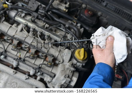 An auto mechanic checks the oil level in a car engine during routine maintenance.  - stock photo
