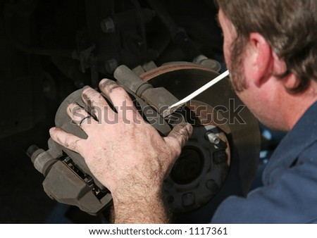 An auto mechanic removing the brake housing from a front disc brake. - stock photo