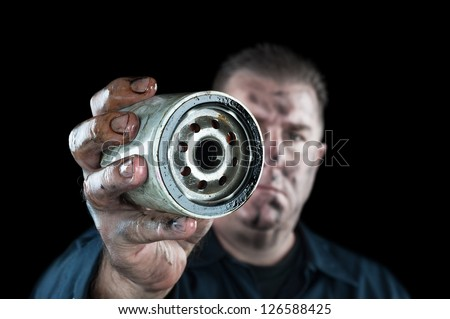 An auto mechanic showing a dirty oil filter during general car maintenance - stock photo