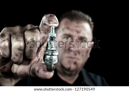 An auto mechanic shows a damaged and worn spark plug as he performs a tune up. - stock photo