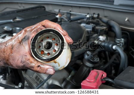 An auto mechanic shows an old, dirty oil filter just removed from a car during general maintenance - stock photo