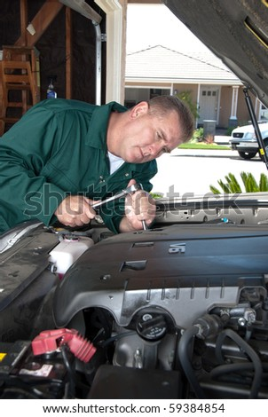 An auto mechanic uses a socket wrench to conduct maintenance and repair a car engine. - stock photo