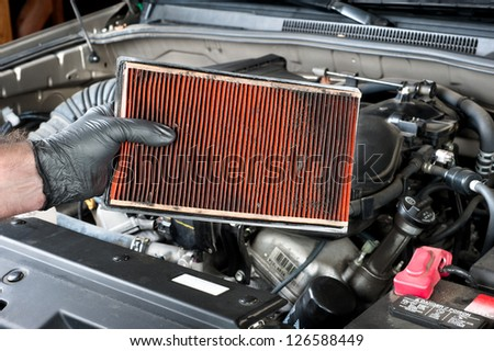 An auto mechanic wearing protective work gloves holds a dirty, clogged air filter over a car engine during general auto maintenance. - stock photo