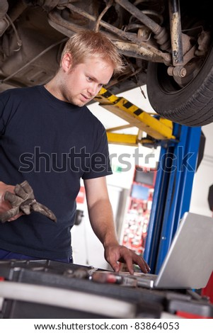 An automechanic referring to a laptop for the service order or manual - stock photo