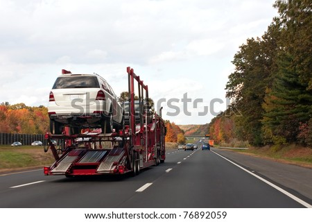 An automotive car carrier truck driving down the highway with a full load of new vehicles. - stock photo