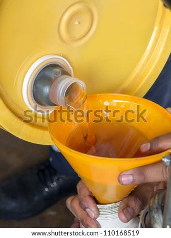 An automotive mechanic changes the oil - stock photo