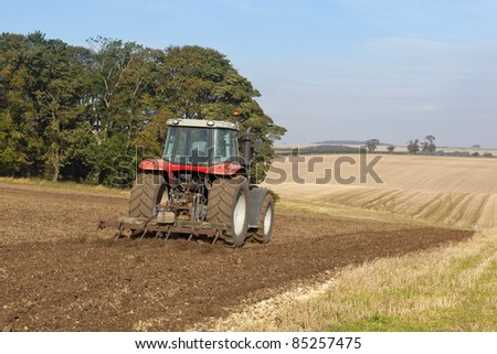 an autumn landscape with a red tractor cultivating a hillside under a blue sky