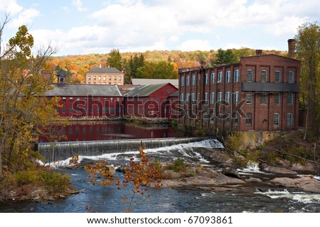 An Autumn river scene with some falls and old mill buildings alongside with colorful foliage on the horizon. - stock photo