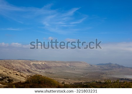 An autumn valley with bushes and blue sky