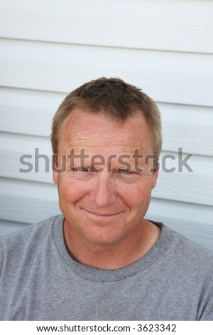 An average 40 year-old man relaxing on his deck.  He's smiling cause he uses your product! - stock photo