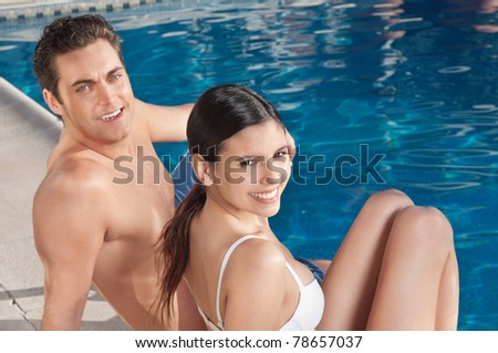 An beautiful young couple relaxing by the poolside - stock photo