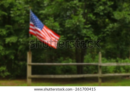 An blurred American flag on a fence post blowing in the wind on a summer day with room for your text to be used as a background. - stock photo