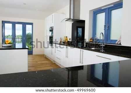 An brand new open plan kitchen and dining area in a large contemporary property - stock photo