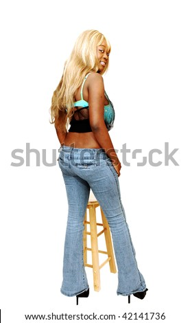 An busty young Jamaican girl in jeans whit long blond hair and high heels standing in a studio for white background.