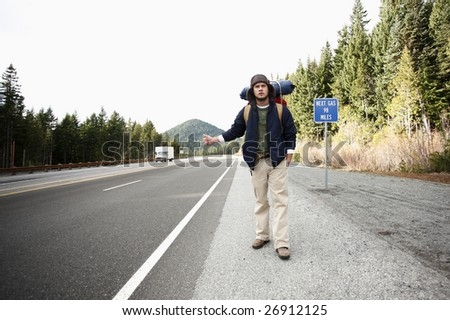 An camper hitchhiking on a mountain road. - stock photo