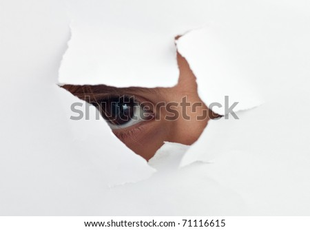 An  child's eye looking through a hole in a  white sheet of paper - stock photo