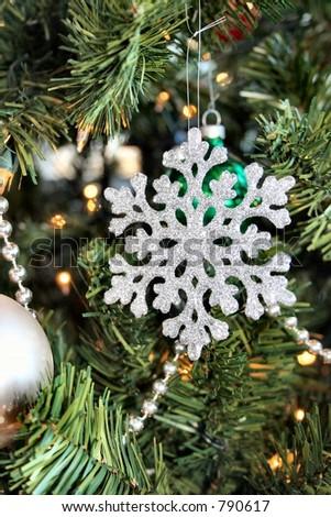 An Christmas tree ornament shaped like a snow flake. - stock photo
