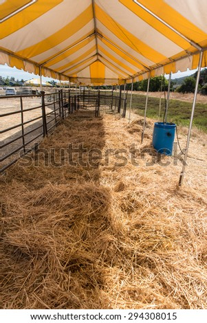 An corral with a fence on one side covers an area of hay on the ground - stock photo