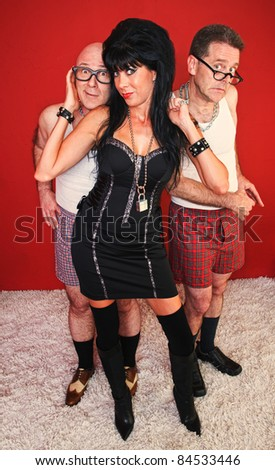 An eager dominatrix woman poses with two of her clients behind her. - stock photo