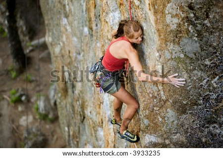 An eager female climber on a steep rock face looks for the next hold - viewed from above.  Shallow depth of field is used to isolated the climber with the focus on the head. - stock photo