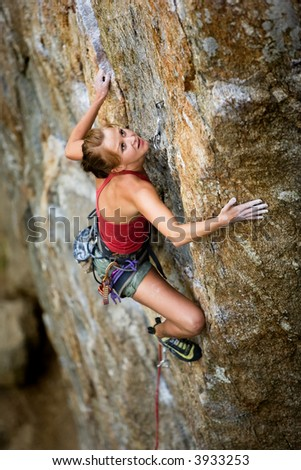 An eager female climber on a steep rock face looks for the next hold - viewed from above.  Shallow depth of field is used to isolated the climber. - stock photo