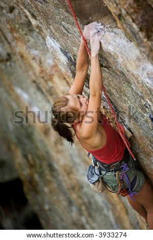 An eager female climber on a steep rock face looks for the next hold - viewed from above.  Shallow depth of field is used to isolated the climber with the focus on the head.