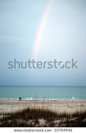 An early morning rainbow seen over the ocean from the beach in Florida - stock photo
