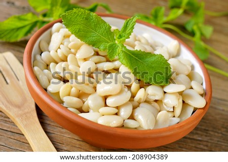 an earthenware bowl with cooked white beans on a rustic wooden table - stock photo