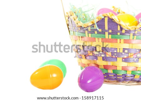 An Easter basket with plastic eggs isolated on white. - stock photo