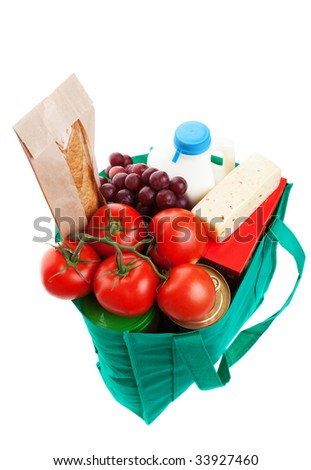 An eco-friendly, reusable, green cloth bag full of groceries.  Shot on white background. - stock photo