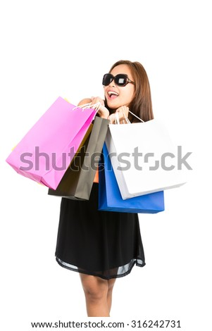 An ecstatic fashionably dressed Asian female shopper hugs and holds department store shopping bags while showing playful and joyful emotion with mouth open and enormous smile. Isolated vertical - stock photo