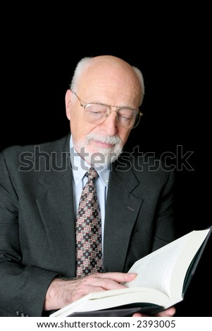 An educated senior man reading a book.  Isolated against a black background. - stock photo