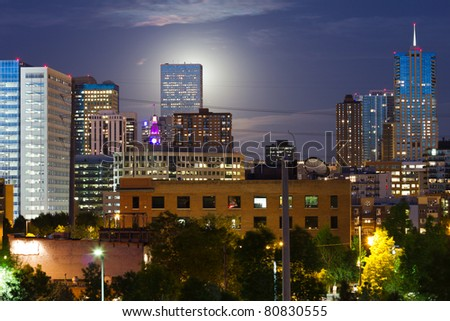 An eerie glowing moon rises  behind a tall skyscraper in the Denver Colorado skyline. - stock photo
