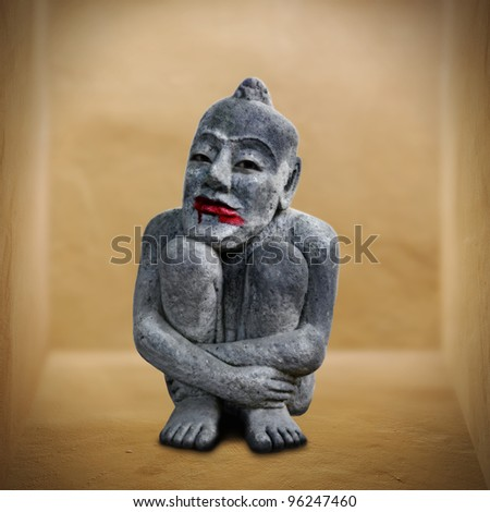 An eerie stone idol with blood on its lip in a rustic box for Halloween concept. - stock photo