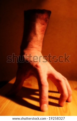 An effects image of a disembodied hand under tungsten lighting on a wooden board with a heavy shadow. Intentionally semi-blurred. - stock photo