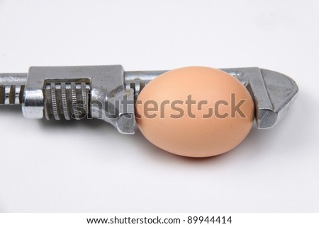 An egg in a wrench - Dangerous stressed situation concept - stock photo