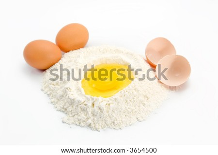 An egg in some flour preparing for baking with eggs and egg shells on the sides