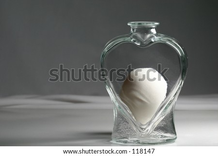An egg inside a heart shaped vase, possibly symbolizing love and fertility. - stock photo