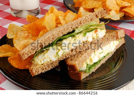 An egg salad sandwich and chips - stock photo