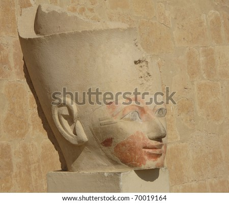 An Egyptian Statue of a man's head outside of a ruin.