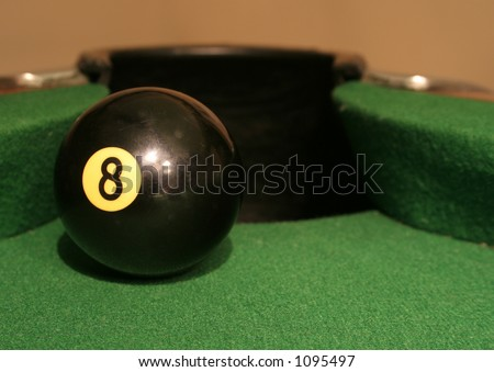 An eight ball sitting at the edge of the corner pocket.