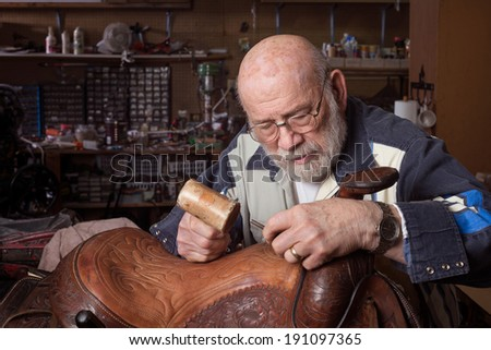 An eighty year old saddle repairman working at his craft. - stock photo