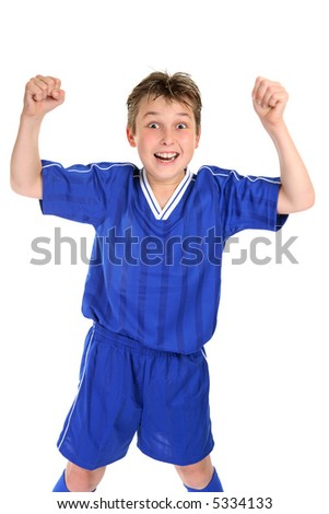 An elated boy celebrates with two fists in the air