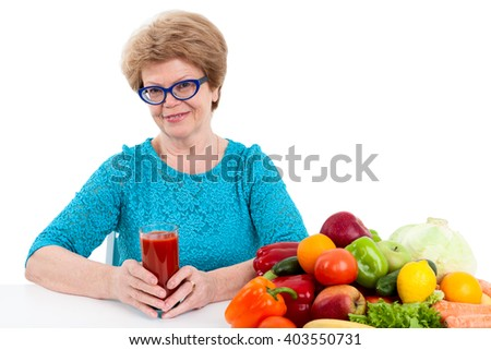 An elder woman holding glass of red tomato juice in hands, fresh fruits and vegetables are on table, isolated on white background - stock photo