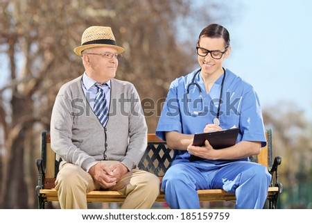 An elderly and a doctor sitting outdoors  - stock photo
