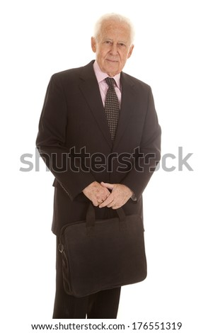 An elderly business man holding a briefcase. - stock photo