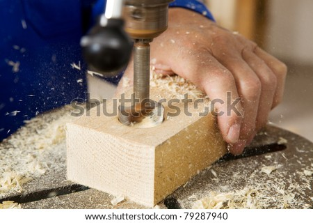 An elderly carpenter in a drill in a joinery - stock photo