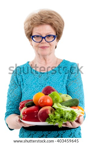 An elderly Caucasian woman portrait with full of fruit and vegetable plate, isolated white background - stock photo