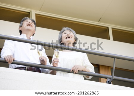 An elderly couple drinking champagne on a balcony