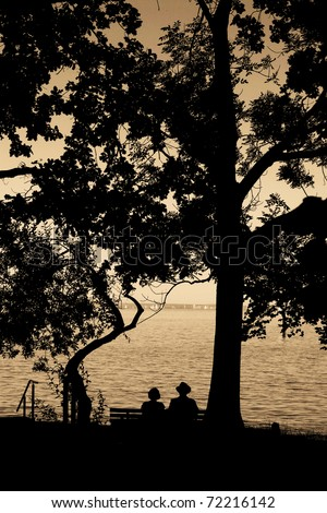 an elderly couple enjoying their retirement on a bench...... - stock photo